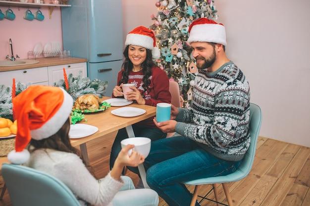 Beeld van mooie familiezitting bij tabel en bekijk elkaar. ze houden bekers in handen. mensen glimlachen naar elkaar. er zijn kalkoen en mandarijnen op tafel. Premium Foto