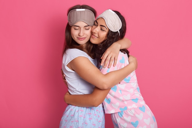 Beeld van mooie mooie knappe vriendschappelijke zusters die elkaar koesteren, ogen sluiten, gezichtsuitdrukking hebben, die naar bed gaan Gratis Foto