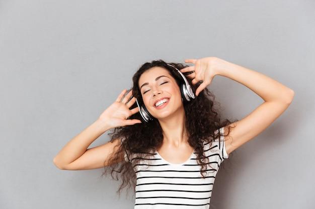 Beeld van tevreden jonge vrouw in gestreepte t-shirt die van favoriete liederen het luisteren melodieën via hoofdtelefoons met gesloten ogen over grijze muur genieten Gratis Foto