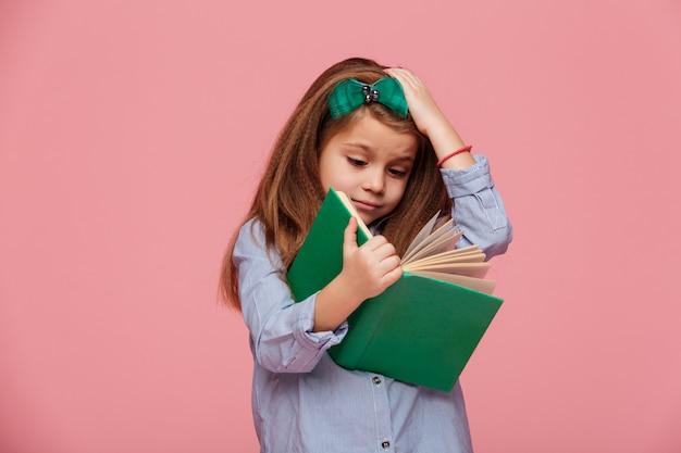 Beeld van vermakelijk meisje in overhemd dat haar hoofd grijpt terwijl het lezen van boek dat studie moe is Gratis Foto