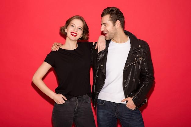 Beeld van vrolijk punkpaar dat en samen over rode muur koestert stelt Gratis Foto