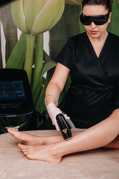 Been epileren procedure met laser gedaan in een cosmetologie kliniek voor een jonge vrouw Premium Foto