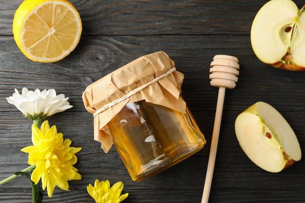 Beer, appel, citroen, bloemen en pot met honing op houten achtergrond Premium Foto