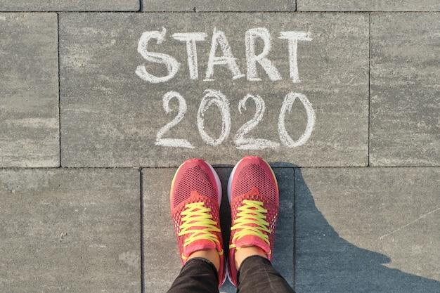Begin 2020, tekst op grijze stoep met benen van de vrouw in sneakers, bovenaanzicht Premium Foto