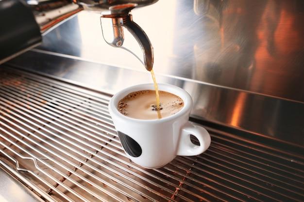 Begin uw dag met een kopje aromatische drank. stijlvolle zwarte espresso machine voor het zetten van koffie, geschoten in café. Gratis Foto