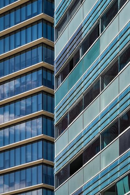 Beglaasde balkons en ramen van de gevels van twee stedelijke gebouwen in blauwachtige en groenachtige tinten Premium Foto