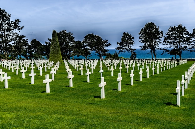 Begraafplaats met witte stenen kruisen omgeven door groene bomen onder de bewolkte hemel Gratis Foto