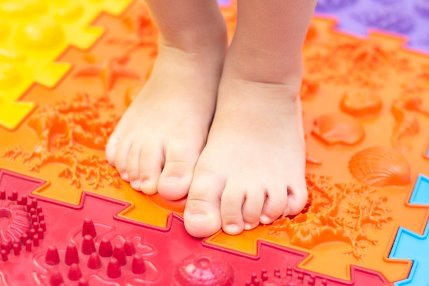 Behandeling en preventie van platvoeten bij kinderen. klein kind loopt blootsvoets op een orthopedische mat puzzel. gymnastiek voor voeten is nuttig voor het hele lichaam Premium Foto