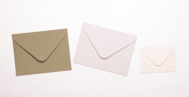 Beige en witte enveloppen op een geïsoleerd wit Premium Foto