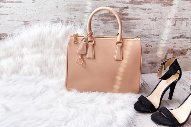 Beige tas en zwarte schoenen op wit bont Premium Foto