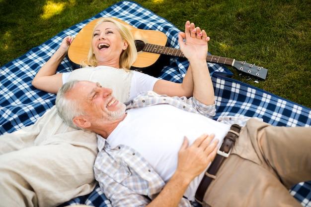 Bejaard paar dat bij de picknick lacht Gratis Foto