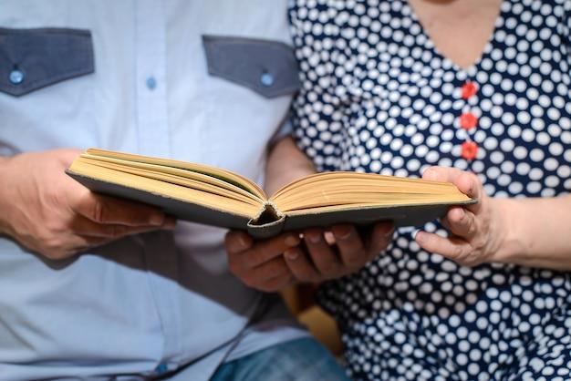 Bejaard paar die een boek samen close-up lezen Premium Foto