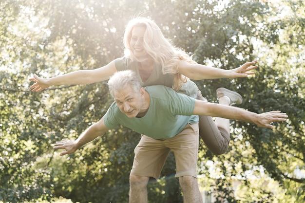 Bejaard paar die rond in het park voor de gek houden Gratis Foto