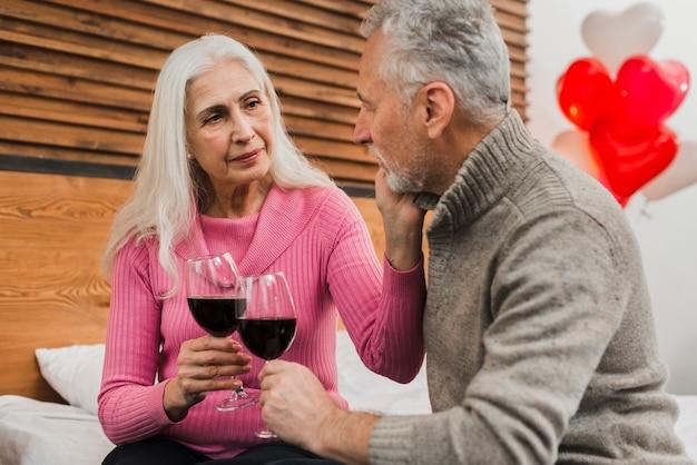 Bejaard paar op bed het drinken wijn Gratis Foto