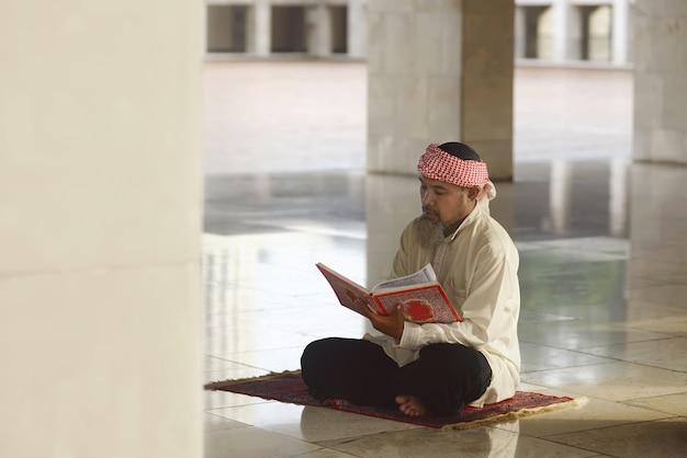 Bejaarde aziatische moslimmens die de koran leest Premium Foto