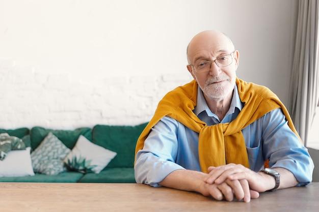 Bejaarde bebaarde zakenman stijlvolle elegante kleding dragen zit aan zijn bureau in modern interieur met bank op achtergrond. mensen, levensstijl, veroudering, zaken, vrije tijd en mode-concept Gratis Foto