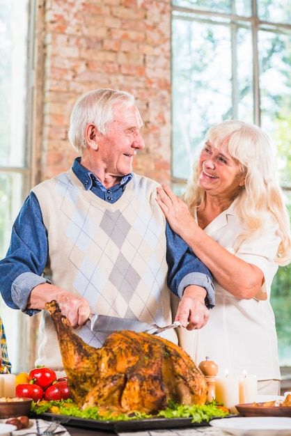 Bejaarde die gebakken kip snijdt bij lijst dichtbij vrouw Gratis Foto