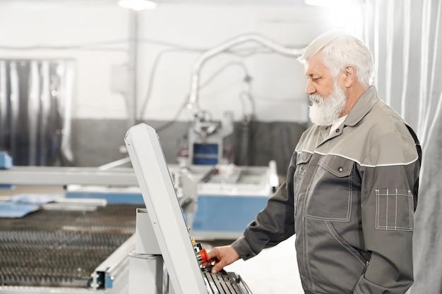 Bejaarde die met lasersnijmachine werkt aan fabriek. Gratis Foto