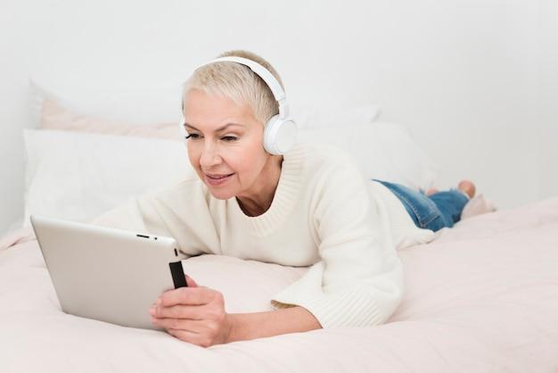 Bejaarde die tablet bekijkt en aan muziek op hoofdtelefoons luistert Gratis Foto