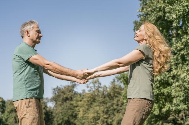 Bejaarde echtpaar dansen in het park Gratis Foto
