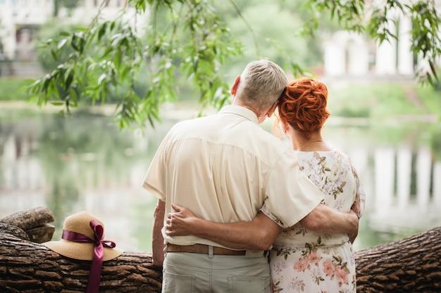 Bejaarde echtpaar wandelen in het park, liefhebbers, liefde buiten de tijd, zomerwandelingen Premium Foto