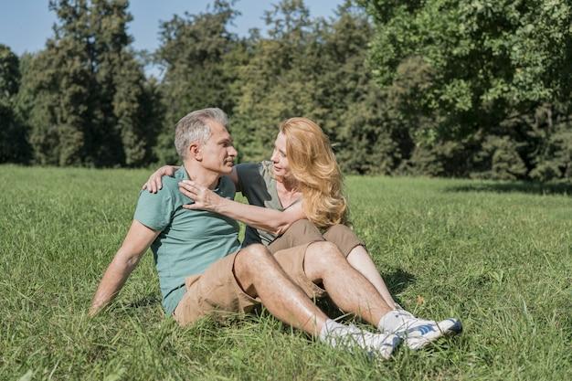 Bejaarde echtpaar zitten samen op gras Gratis Foto
