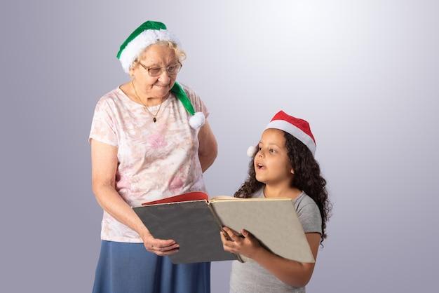 Bejaarde en kind die met kerstmishoed een boek op grijs lezen Premium Foto