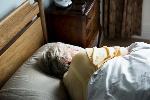 Bejaarde kaukasische vrouwenslaap op het bed Premium Foto