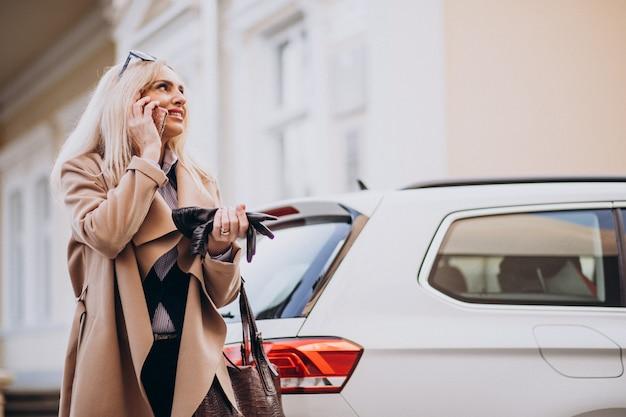 Bejaarde onderneemster die op telefoon door haar elektroauto spreekt Gratis Foto