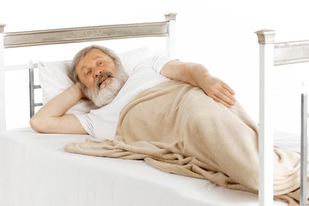 Bejaarde oude mens die in een geïsoleerd het ziekenhuisbed terugkrijgt Gratis Foto