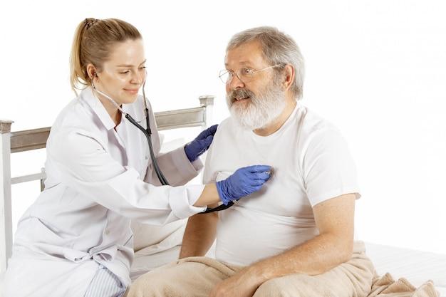 Bejaarde oude mens die in een het ziekenhuisbed terugkrijgen dat op wit wordt geïsoleerd Gratis Foto
