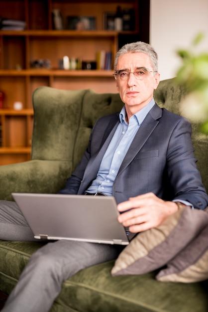 Bejaarde zakenman die laptop met behulp van Gratis Foto