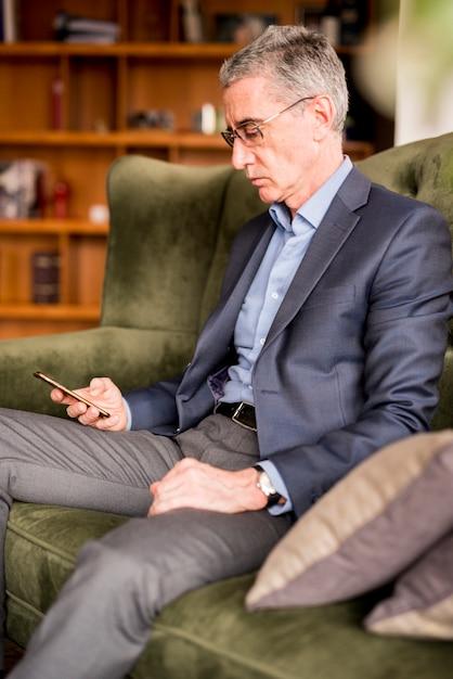 Bejaarde zakenman die mobiele telefoon met behulp van Gratis Foto