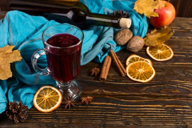 Beker glühwein met kruiden, fles, sjaal, droge bladeren en sinaasappelen op een houten tafel. herfststemming, methode om warm te blijven in de kou, copyspace. Premium Foto