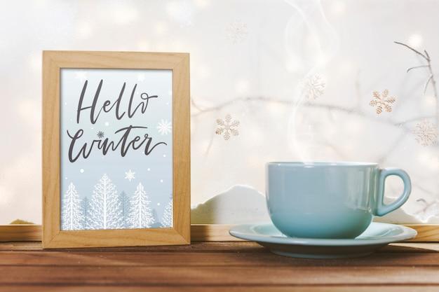 Beker in de buurt van frame met hallo winter titel op houten tafel in de buurt van bank van sneeuw Gratis Foto