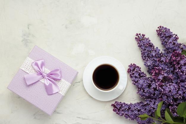 Beker met een koffie, een geschenkdoos en een mooi wit oppervlak Premium Foto