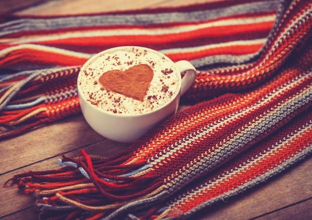 Beker met koffie en vorm van het cacaohart erop en sjaal Premium Foto