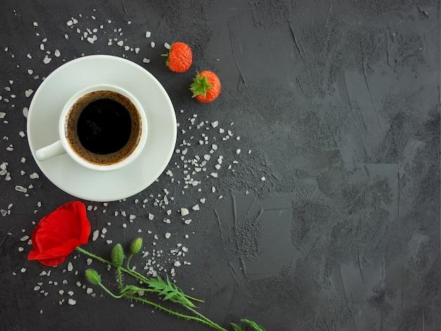 Beker met koffie op een textuur tafel met poppy bloem en aardbeien Premium Foto