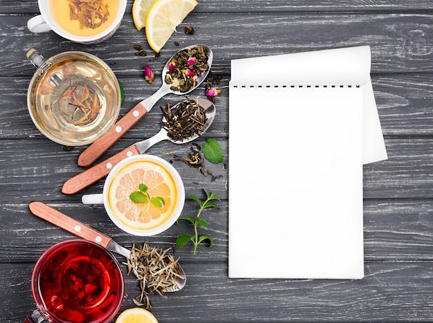 Beker met thee en kruiden naast en notebook Gratis Foto