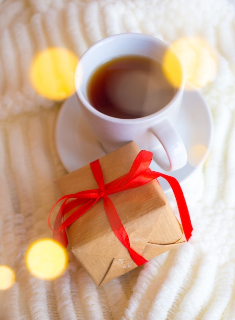 Beker met thee op een lichte achtergrond en een cadeau voor valentijnsdag. romantisch moederdagontbijt. Premium Foto