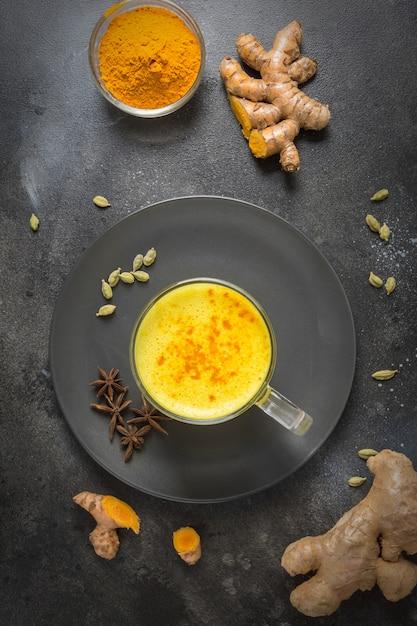 Beker van ayurvedische gouden kurkuma latte melk met kurkuma poeder en anijs ster Premium Foto