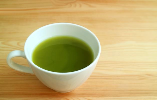 Beker van hete matcha groene thee geïsoleerd op natuurlijke bruine houten tafel Premium Foto