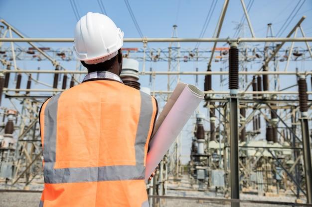Bekijk formulier achterkant knappe engineering man met papieren projecten plan en draag veiligheidshelm voor high power power plant. achteraanzicht van aannemer op achtergrond van elektriciteitscentralegebouwen. Premium Foto