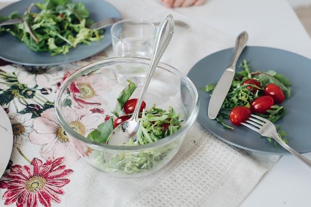 Bekijk van bovenaf van gezonde tomaten en groenen liggend op een grijze plaat op keuken. lekkere verse groenten, mes en vork liggend op tafel in café. concept keuken, dieet en voeding. Gratis Foto