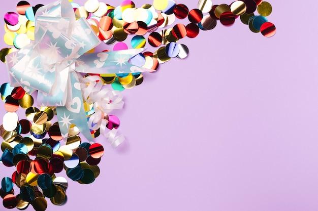Bekleed met gekleurde confetti en een cadeau strik op een paarse achtergrond met lege advertentieruimte. Premium Foto