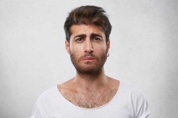 Beklemtoonde bebaarde man met droevige uitdrukking die oorbel en wit t-shirt draagt die zijn lip buigt die droevig nieuws kent. verbijsterd mannetje. mensen en negatieve emoties concept Gratis Foto