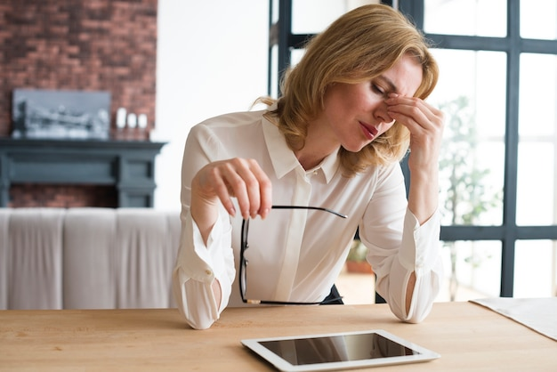 Beklemtoonde bedrijfsvrouw bij lijst met tablet Gratis Foto