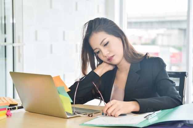 Beklemtoonde bedrijfsvrouwenzitting in het bureau Premium Foto