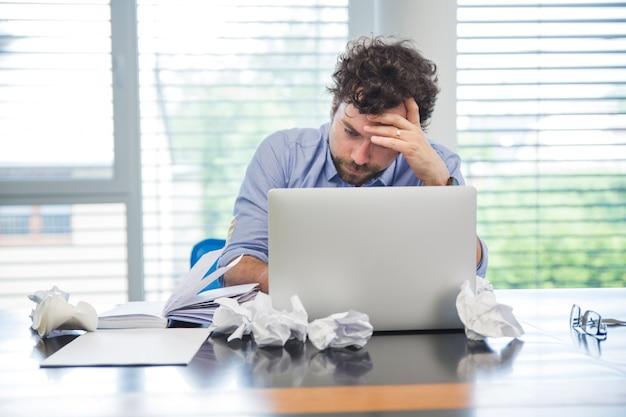 Beklemtoonde man met laptop in kantoor Gratis Foto
