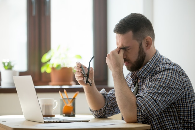 Beklemtoonde mannelijke masserende neusbrug die aan hoofdpijn lijdt Gratis Foto